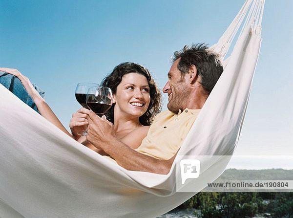 Paar in einer Hängematte mit Wein