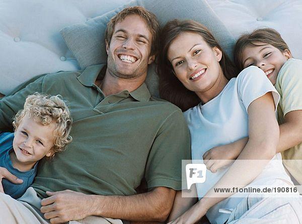 Familie auf Kissen liegend