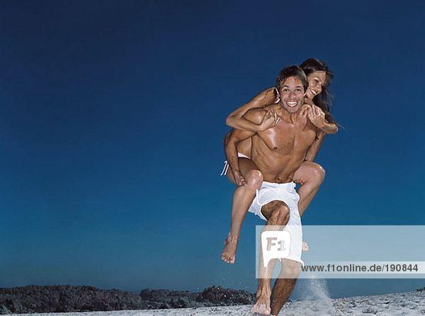 Mann  der seiner Frau ein Huckepack gibt.