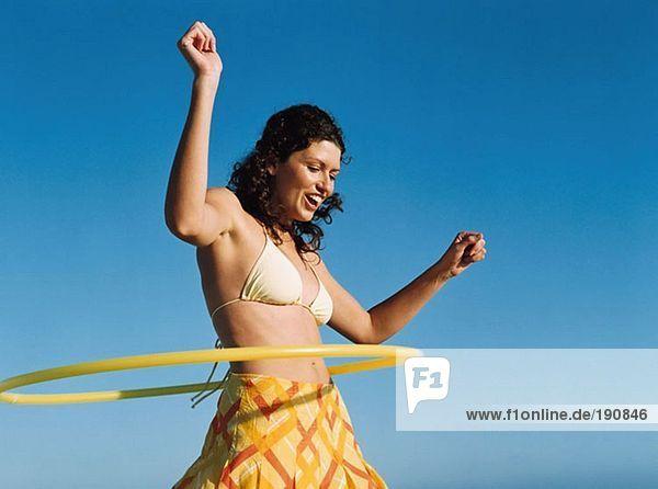 Frau spielt mit Hula Hoop