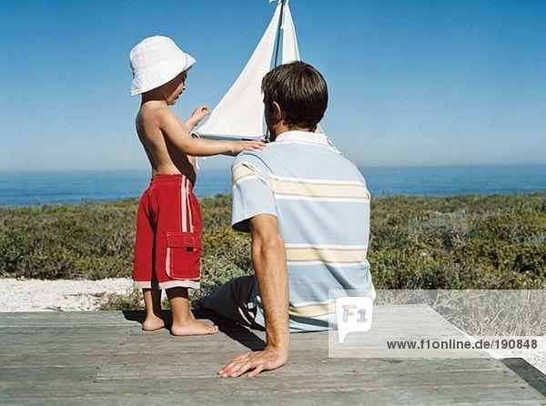 Vater und Sohn mit Spielzeugboot