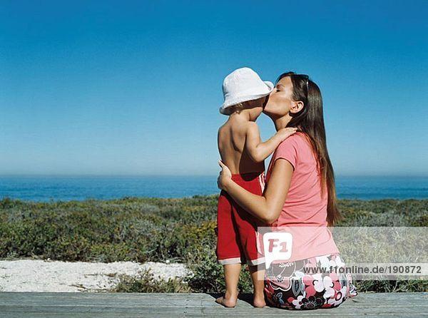 Mutter küsst ihren Sohn auf die Stirn.
