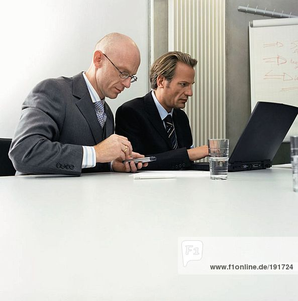 Businessmen using laptop and palmtop