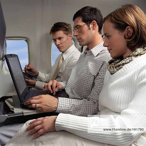Geschäftsleute  die in einem Flugzeug arbeiten