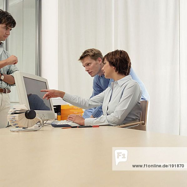Drei Büroangestellte am Schreibtisch