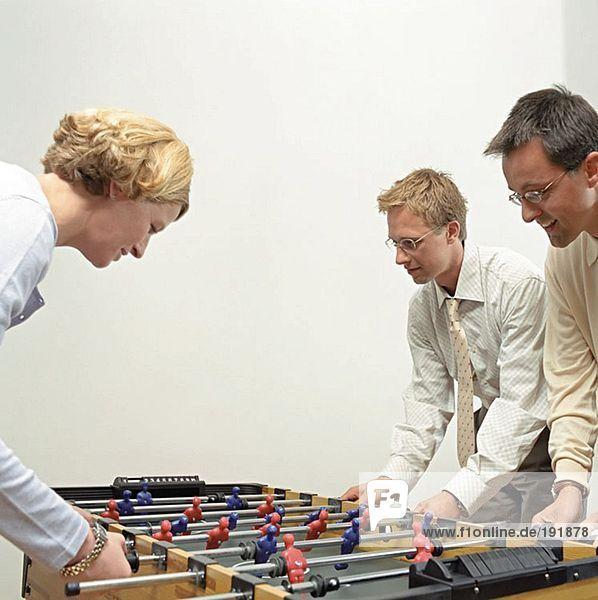 Büroangestellte spielen Tischfußball
