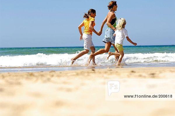 Seitenansicht Frau mit ihren beiden Töchtern am Strand