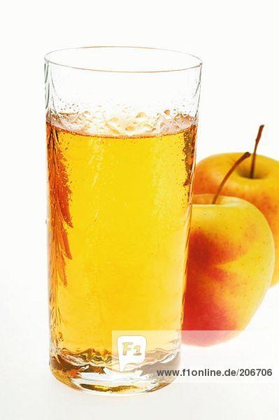 Glas Apfelsaft neben zwei frischen Äpfeln