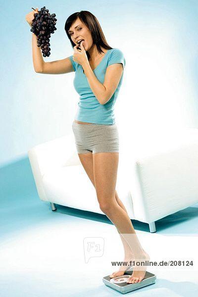 Junge Frau  mit Weintrauben auf einer Personenwaage stehend