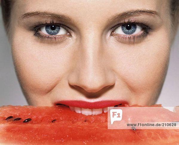 Frau beißt in Wassermelone
