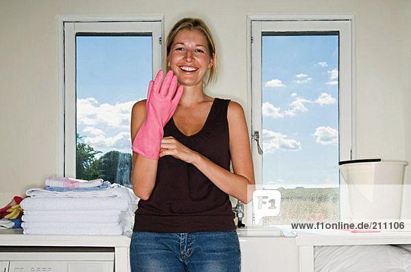 Frau zieht Gummihandschuh an