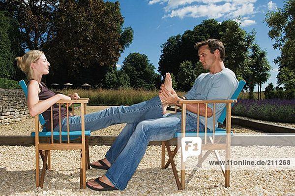 Mann  der die Füße seiner Freundin massiert.