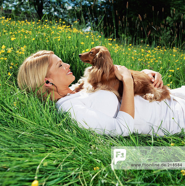Frau auf dem Feld liegend mit Hund