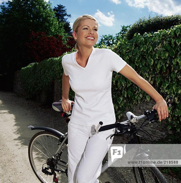 Frau mit Fahrrad auf dem Weg