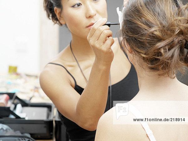 Kosmetikerin beim Auftragen von Mascara