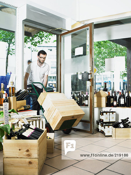 Mann schiebt Wagen mit Weinkisten in den Laden