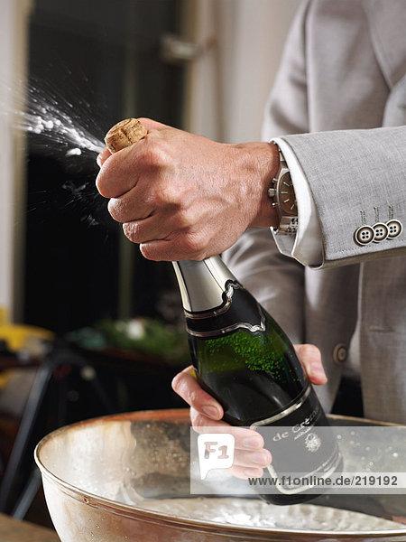 Mann öffnet Champagnerflasche