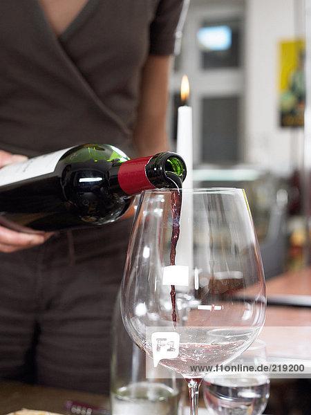 Rotwein ins Glas gießen