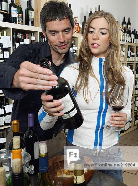 Paar beim Betrachten der Weinflasche