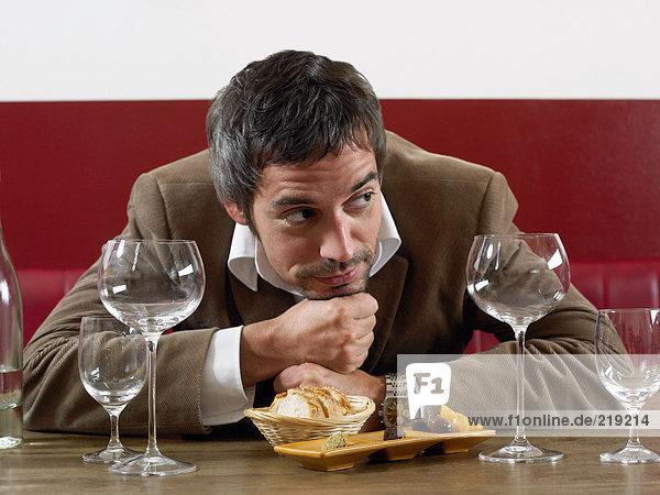 Mann bei Tisch mit Brot und Oliven