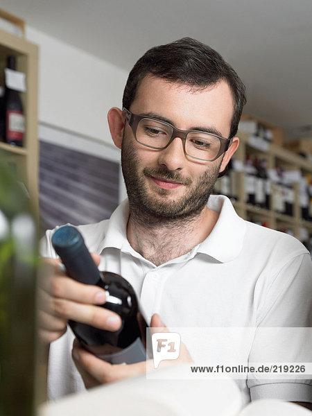 Bärtiger und bebrillter Mann mit Weinflasche
