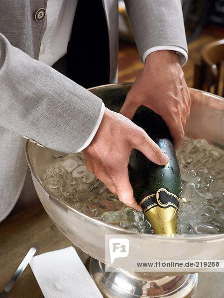 Mann nimmt Champagnerflasche aus Eiskübel