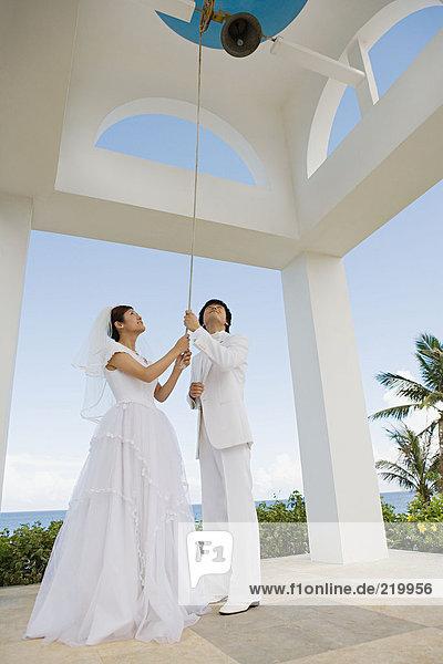 Braut und Bräutigam läutet Kirchenglocke