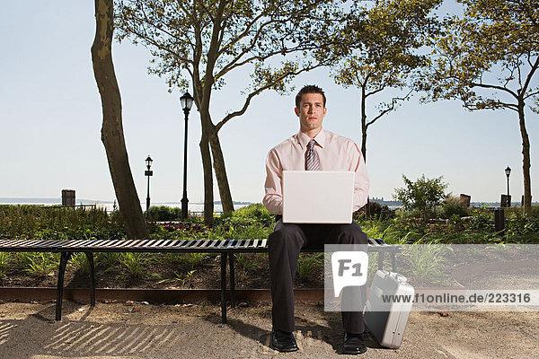 Mann Telearbeit in einem Park