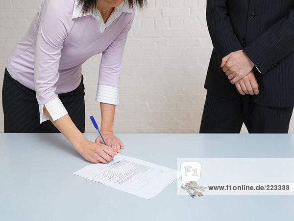 Frau  die einen Vertrag unterschreibt