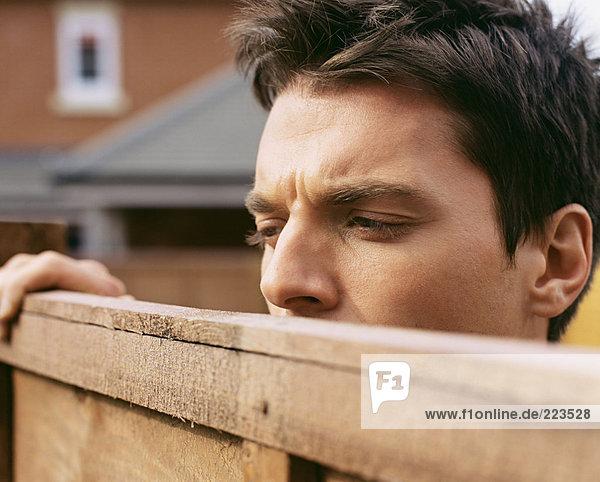 Mann schaut über den Gartenzaun