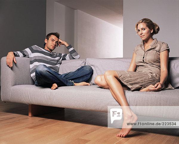 Junges Paar auf einem Sofa sitzend