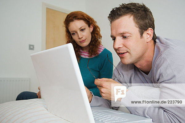 Paar mit Laptop im Schlafzimmer