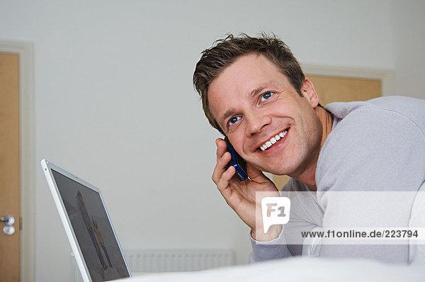 Mann  der einen Laptop-Computer und ein Mobiltelefon benutzt.