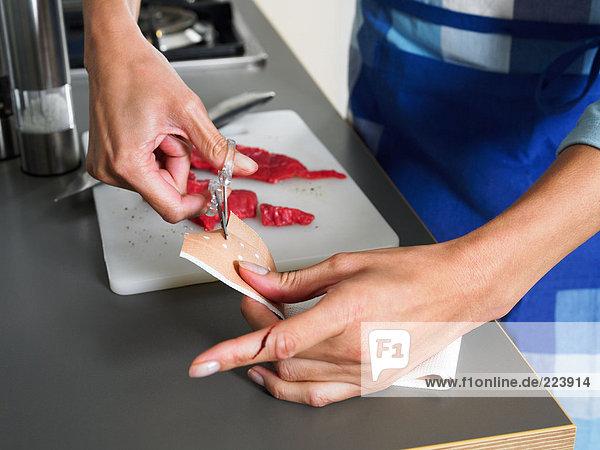 Frau schneidet Klebepflaster zum Aufstecken auf den Finger