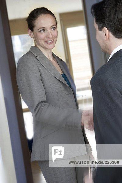 Geschäftsfrau Hand mit Geschäftsmann an Tür schütteln