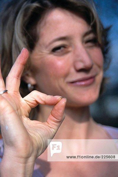 Porträt von Frau zeigt Ok-Zeichen