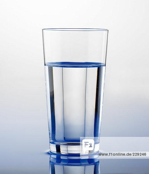 Wasserglas auf Wasserfläche stehend