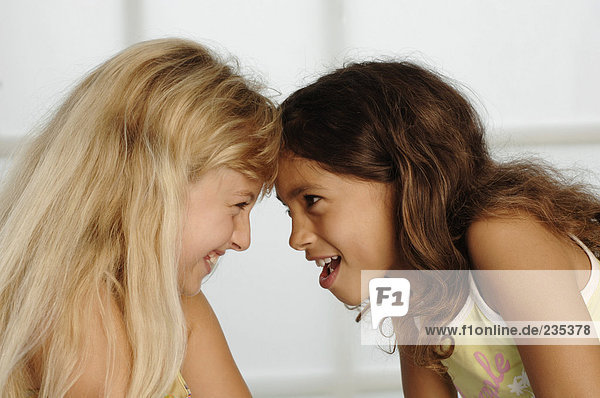 Two girls (8-11) head to head  smiling  side view