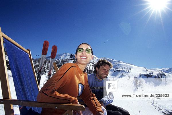 Paar entspannt auf dem Liegestuhl in den Alpen  lächelnd