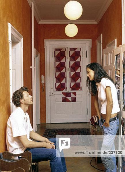 hellhäutiges Paar in Wohnung Korridor diskutieren
