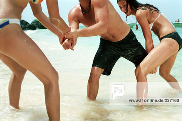 two women and one man playing on the beach