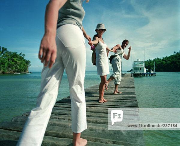 junge Menschen im tropischen Urlaub Wandern am Pier zu Boot
