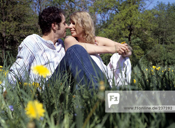 couple in love sitting in the grass flirting