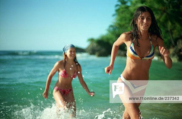 zwei Frauen laufend aus dem Meer auf tropischen Strand