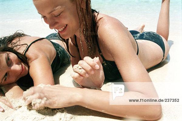 zwei junge Frauen liegen in den Sand am Strand entspannen und sprechen