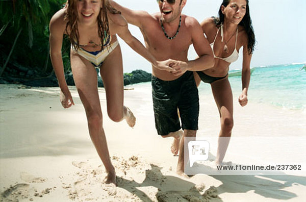 two women and one man posing on tropical beach