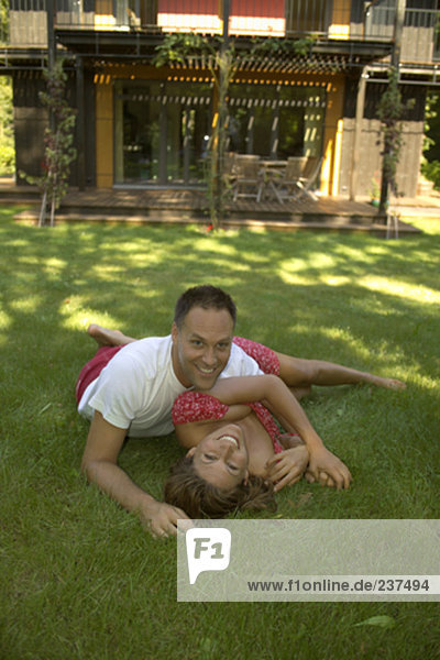 portrait of couple lying in the grass  house in background