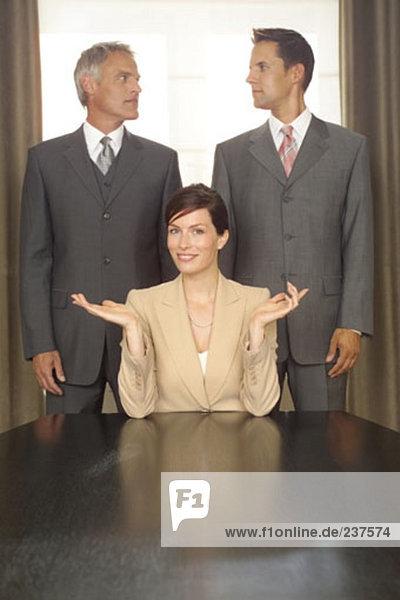 junge Geschäftsfrau sitzt am Tisch während zwei Unternehmer hinter ihr Blick auf