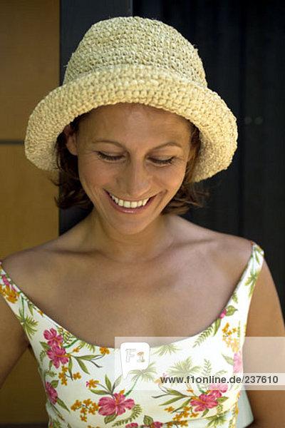 Portrait of glückliche Frau in flowery Kleid tragen ein Strohhut