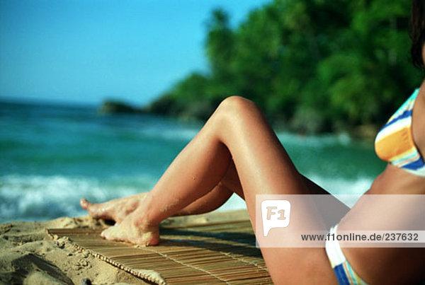 junge Frau im Sitzen auf einem tropischen Strand Bikini Nahaufnahme